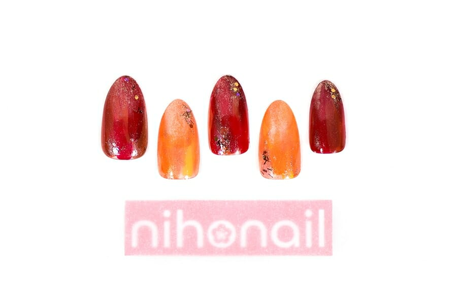 深い赤×オレンジのコントラストが印象的な塗りかけネイル