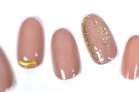 ゴールドパーツとラメが映えるくすみピンクの大人っぽネイル